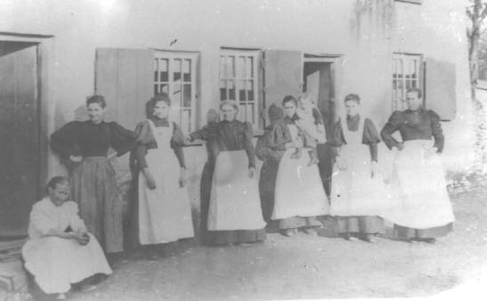 faded photograph of seven ladies in aprons outside a house (source unknown).