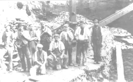 faded photograph of nine workmen (in a quarry?)(source unknown).